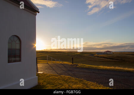An early sunset falls behind a white church in Snaefellsnes peninsula, Iceland, with green fields and blue sky as - Stock Photo