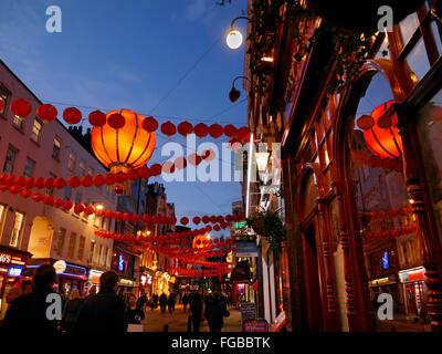 Chinese lanterns lit up on a busy night in Wardour Street Chinatown Soho London UK - Stock Photo