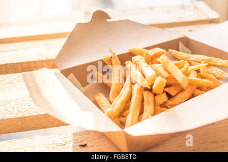 Close-Up Of Fresh French Fries In Cardboard Box On Table - Stock Photo