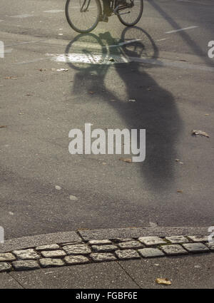 High Angle View Of Person Cycling Shadow On Street - Stock Photo