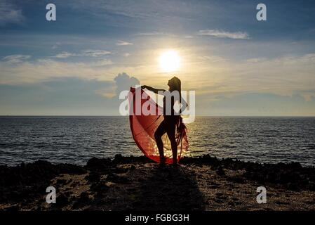 Woman Standing On Cliff By Sea Against Sky During Sunset - Stock Photo