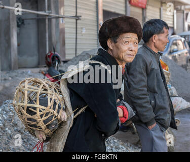 Piggy-back, man with pig in wicker basket, Niujiaozhai Market, Yunnan Province, China - Stock Photo