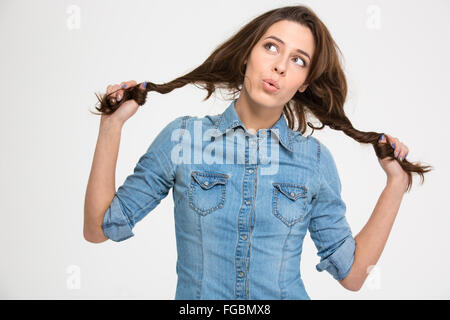 Playful pensive cute young woman grimacing and holding her hair as two braids over white background - Stock Photo