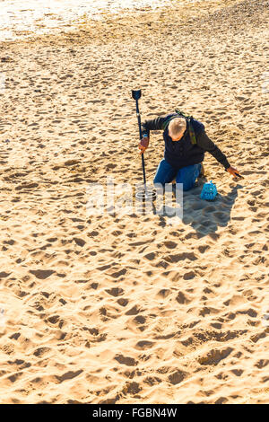 Man using metal detector on sandy at Swanage - Stock Photo