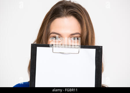 Closeup of cute lovely young woman hiding behind blank clipboard over white background - Stock Photo
