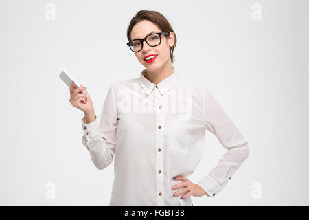Smiling confident young business woman standing and holding smartphone in her hand over white background - Stock Photo