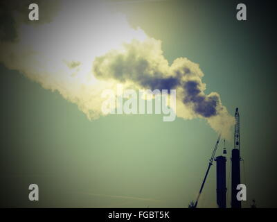 Low Angle View Of Smoke Emitting From Industrial Building Against Sky - Stock Photo