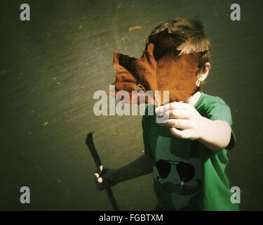 High Angle View Of Boy Hiding Face With Leaf While Standing Against Little Blue River During Autumn - Stock Photo