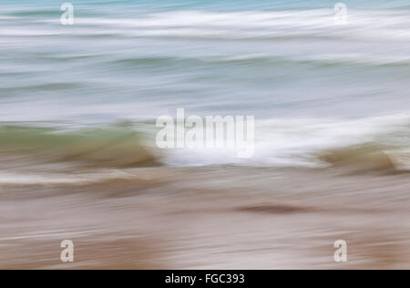Ocean waves crashing on sandy beach abstract background, in-camera motion blur. - Stock Photo