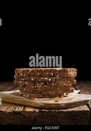 Slices of  Brown Bread (selective focus) on an old wooden table - Stock Photo