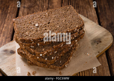 Brown Bread (sliced) on an old wooden table (selective focus) - Stock Photo