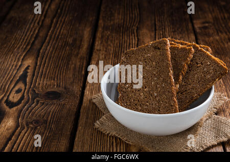 Some slices of brown Bread (selective focus) on wooden background - Stock Photo