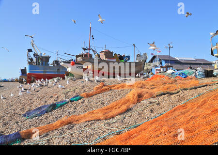 Fishing boats drying their nets on Hastings Stade fishermen's beach, East Sussex, England, UK - Stock Photo