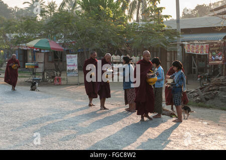Burmese monks on alms round in early morning, receiving food alms from the pople of Shwe Kyet Yet, Mandalay Region, - Stock Photo