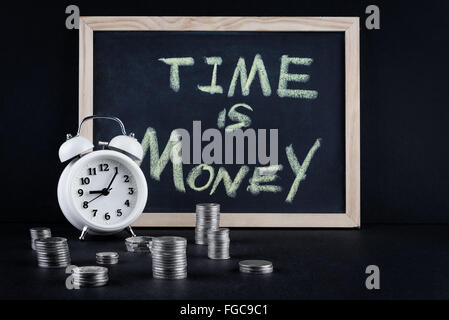Vintage alarm clock showing 5 o'clock and coin towers with chalckboard and 'time is money' text on black background. - Stock Photo