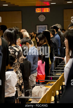Participants taking the oath to become new Canadians in the citizenship ceremony in Vancouver, BC, Canada in November - Stock Photo