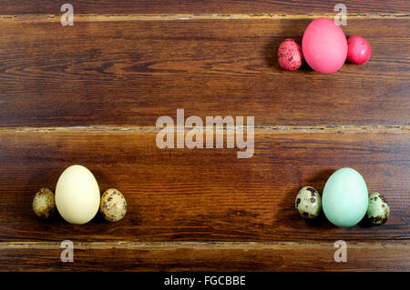 Various eggs and quail eggs with card over wooden background from top