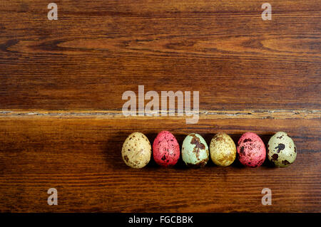 Colourful various quail eggs over wooden background
