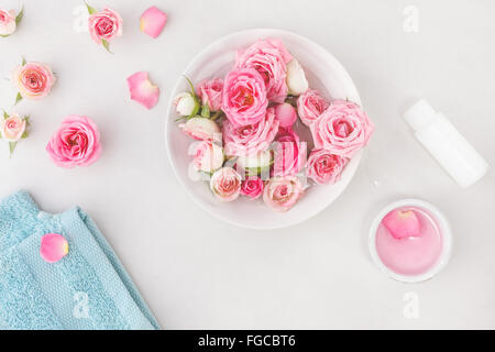 Spa settings with roses. Fresh roses and rose petals in a bowl of water and various items used in spa treatments - Stock Photo