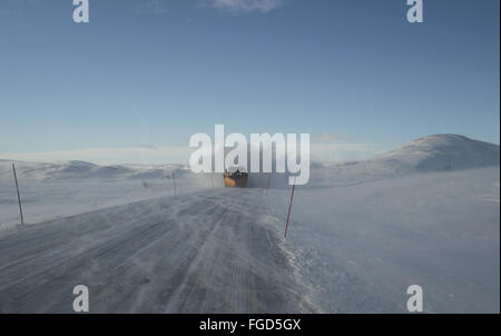 Snowplough clearing snow from road with markers, Kongsfjord, Varanger Peninsula, Finnmark, Norway, March - Stock Photo