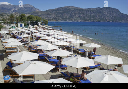 Parasols and tourists on beach, Alimounda Mare Hotel, Pigadia, Karpathos, Dodecanese Islands, Aegean Sea, Greece, - Stock Photo