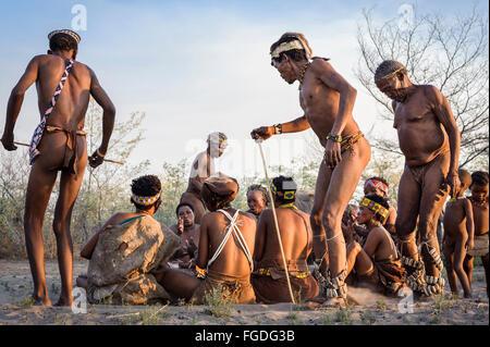 Kalahari San people dancing in circles around people sitting down on the ground and singing. - Stock Photo