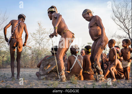 Kalahari San people dancing in circles around people sitting down on the ground and singing. - Stock Photo
