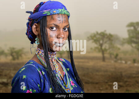 Portrait of a Mbororo woman with typical scars on her face outside her village while the Harmattan wind is blowing - Stock Photo