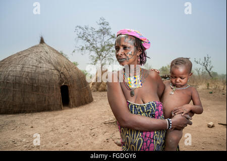 Portrait of a Mbororo woman with the typical scarification on her face holding her child. - Stock Photo