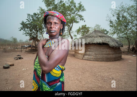 Portrait of a Mbororo woman with scars on her face outside her hut. - Stock Photo