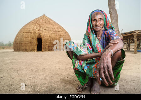 Portrait of an old Mbororo woman sitting down on the ground in front of her hut. - Stock Photo