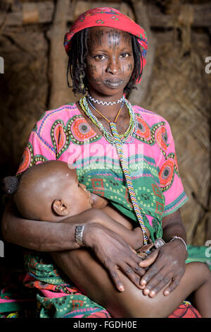 Portrait of a Mbororo woman with the typical scarification on her face holding her child inside a hut. - Stock Photo