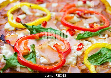 Oven baked pizza topped with halloumi, cottage, mozzarella cheese, spinach, turkey, ham, red and yellow peppers, - Stock Photo