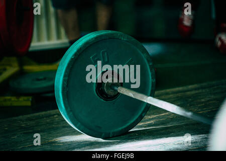 closeup of green barbell plates on a wooden floor in sun - Stock Photo