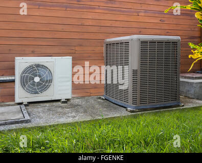 Two different sized air conditioning heat pumps on the side of a house - Stock Photo