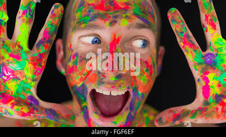 Close up of a man's face covered in coloured paint - Stock Photo