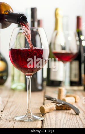 pouring red wine in glass on wooden table near corkscrew and bottle Stock Photo
