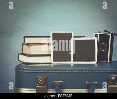 Old photographs, a camera and books are on top of a vintage suitcase with a blue background for a memory concept - Stock Photo