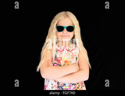 Young girl with long blonde hair wearing sunglasses, smiling - Stock Photo