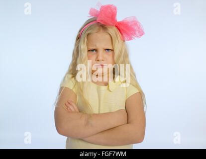 Young girl with long blonde hair and folded arms, frowning with a sad and grumpy expression - Stock Photo