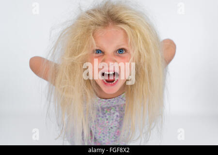 Young girl with messy blonde hair screaming - Stock Photo