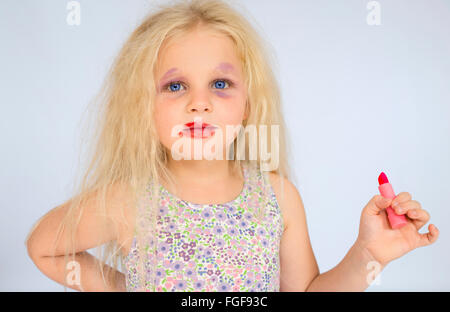 Young girl with blonde hair wearing smudged make up holding a red lipstick - Stock Photo