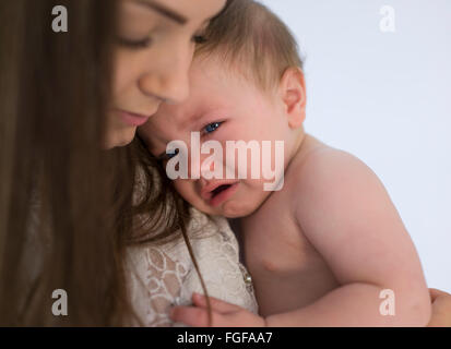 Mother holding baby son in arms crying with a single tear emerging from his eye - Stock Photo