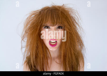 Portrait of a woman with messy disheveled hair with and expression of anger - Stock Photo