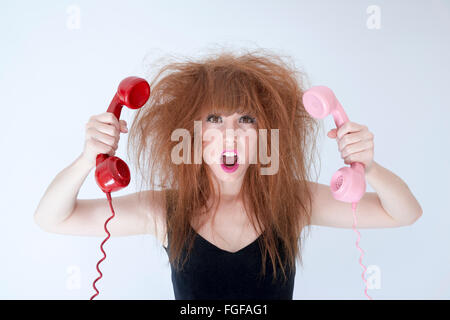 Woman with messy hair holding two retro telephones screaming - Stock Photo