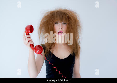 Woman with messy hair holding a red retro telephone with an expression of confusion - Stock Photo