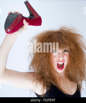 Woman with messy hair holding a red suede high heeled shoe in the air about to strike, screaming - Stock Photo