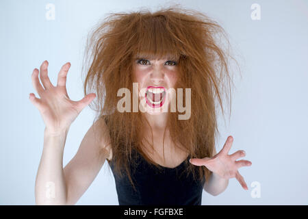 Woman with messy tangled long brown hair about to fight screaming - Stock Photo