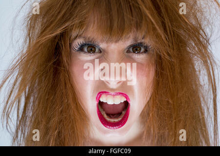 Portrait of a woman with messy disheveled hair with an expression of anger - Stock Photo