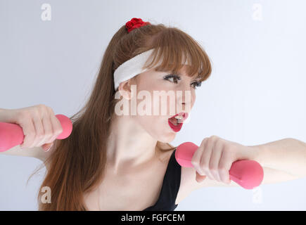 Woman with long brown hair wearing a sweat headband holding pink dumbbells exercising